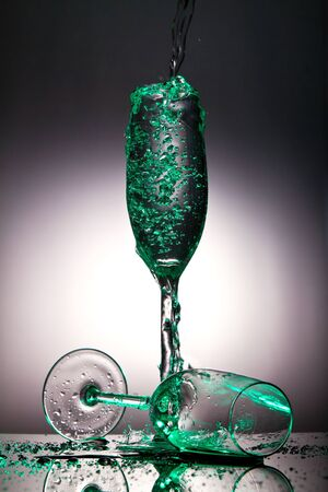 Champaigne glass overflowing with liquid with green tint photo
