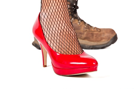 stilletto: Red stilletto shoe in foreground with brown walking shoes in background Stock Photo