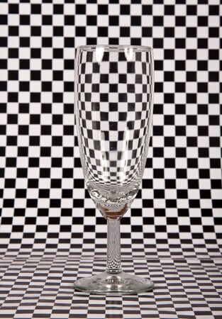 Champagne glass on check background creating a distortion Stock Photo - 13719680