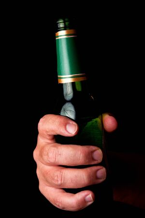 Male hand holding green, empty beer bottle photo