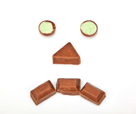 dark face: Sad face made out of chocolate on a white background