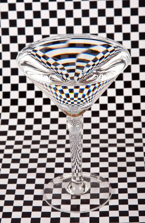Martini glass on check paper creating a distorted image photo