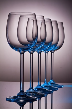 Crystal wine glasses in a row standing on a shiny surface photo