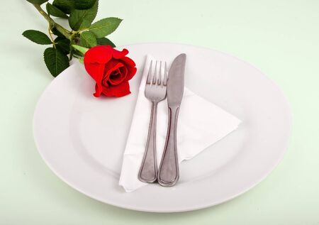 Fork and knife on a white plate decorated with a red flower photo