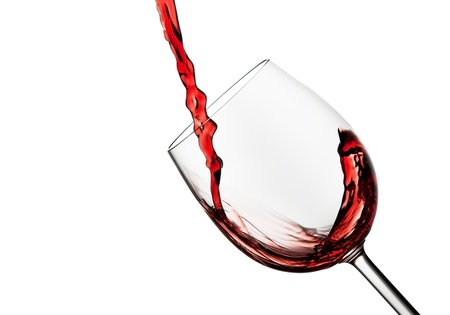 Tilted crystal wine glass with red wine against a white background