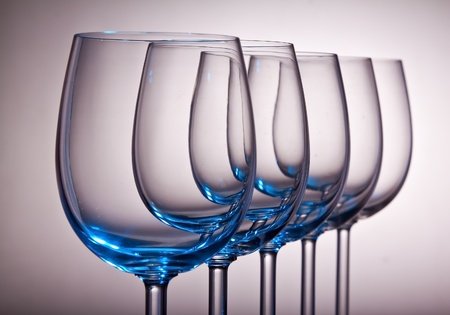 Wine glasses in a row with a blue tint