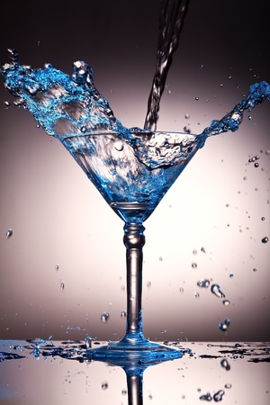 Liquid splash in a martini glass with a blue tint photo