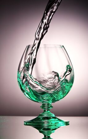 distilled alcohol: Liquid splash in a cognac glass with a green tint