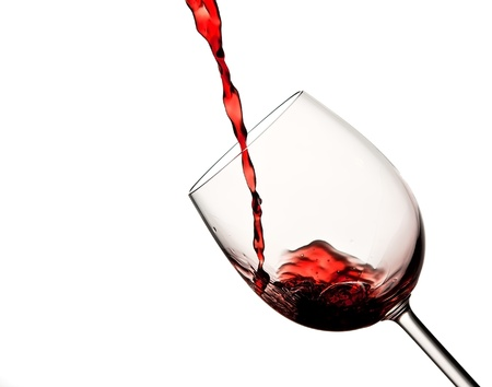 Pouring red wine in wine glass being tilted skew