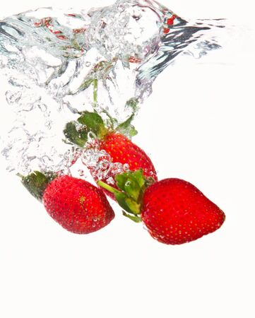 Three strawberries falling into crystal clear water photo