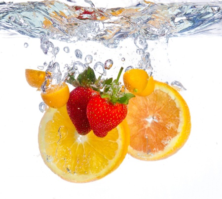 fruit in water: Fruit falling into water clear ripple fresh red orange Stock Photo