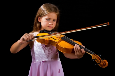 Girl playing violin in pink dress concentration on black photo