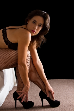 Woman in underwear sit on edge of bed stocking high heals photo