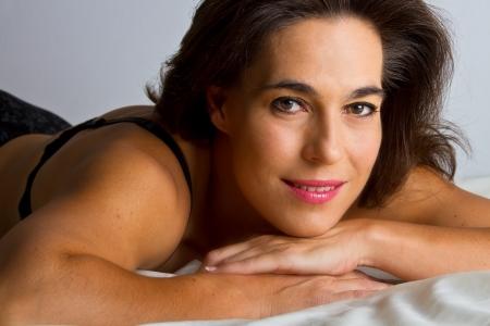 Woman in black underwear lay on bed in studio photo