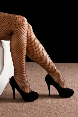 sexually: Woman in underwear sit on edge of bed stocking high heals