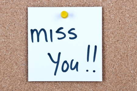 Post it note white with miss you message on cork photo