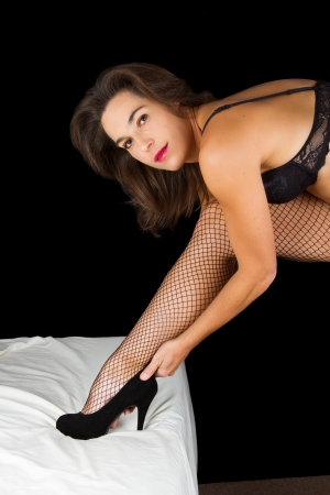 Boudoir woman put on shoes on bed in underwear photo