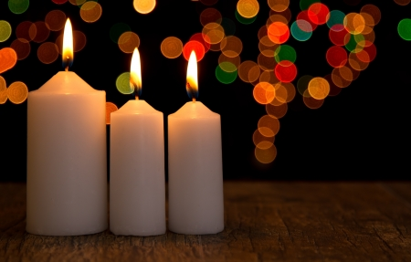 Candle light closeup with bokeh pattern and dark background photo
