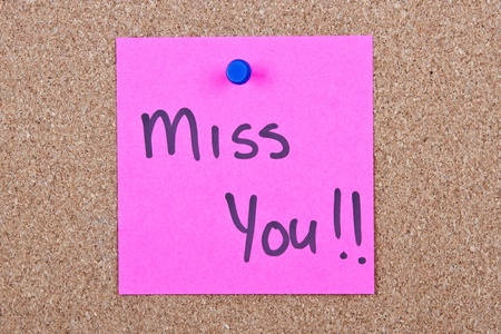 Post it note pink with miss you message on cork photo