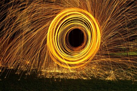 Burning steel wool spin in circles to make patterns in the night Stock Photo - 20821066