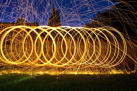 Burning steel wool spin in circles to make patterns in the night photo