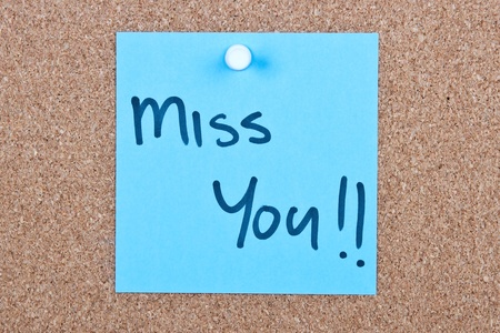 Post it note blue with miss you message on cork photo