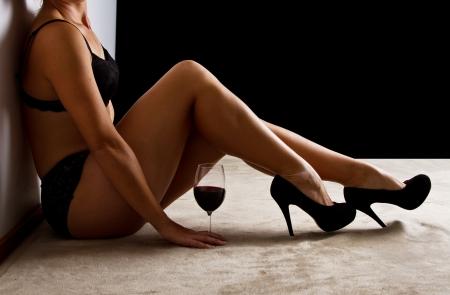 sensuel: Femme en sous-v?tements noirs assis sur les chaussures de sol Banque d'images