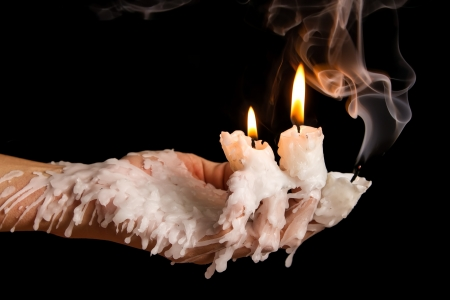 Three candle sticks on fingers buring with wax flow Stock Photo