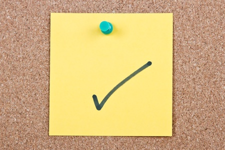 cork sheet: Post it note on wood in yellow with correct mark Stock Photo