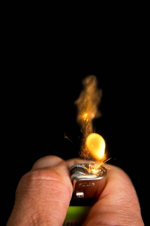 Hand with lighter igniting sparks close-up on dark background photo