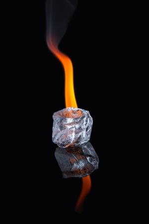 evaporating: Ice cube melting with flame on shiny black surface