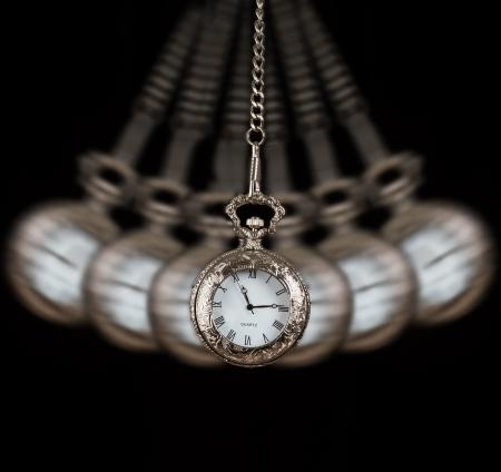 Pocket watch silver swinging on a chain black background to hypnotise Archivio Fotografico