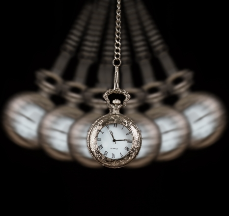 Pocket watch silver swinging on a chain black background to hypnotise Stock Photo
