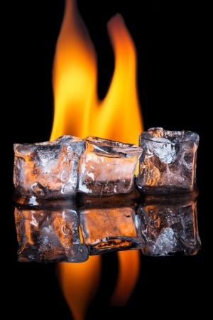 smolder: Ice cubes melting with flame on shiny black surface Stock Photo