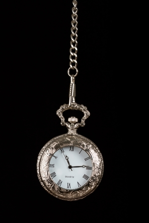 Silver pocket watch hang on chain black background photo