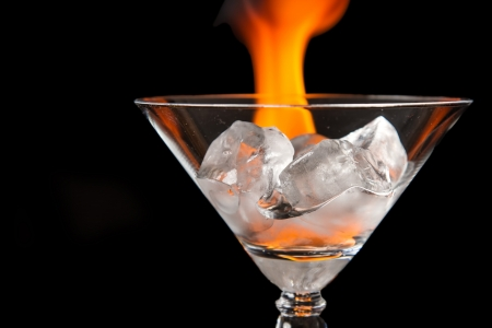 unnatural: Ice cubes melting in glass with flame on shiny black surface Stock Photo