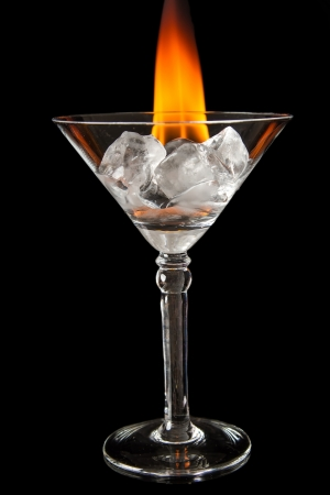 Ice cubes melting in glass with flame on shiny black surface Stock Photo