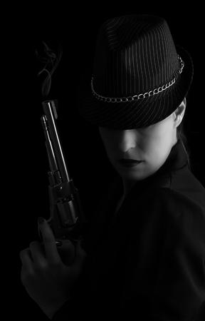 mujer con arma: Mujer peligrosa en negro con plata pistola de fumar y con estilo conversión artística sombrero