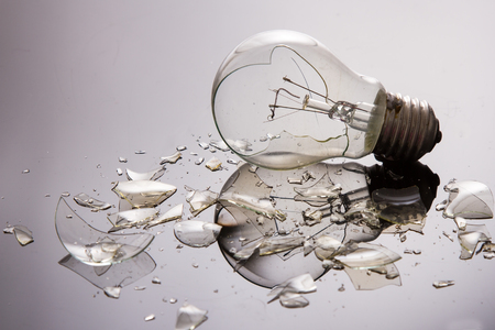 Broken light bulb on shiny surface with pieces backlit