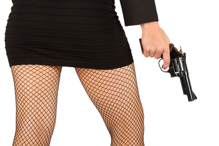 Legs of dangerous woman with handgun and black shoes fishnet stockings photo