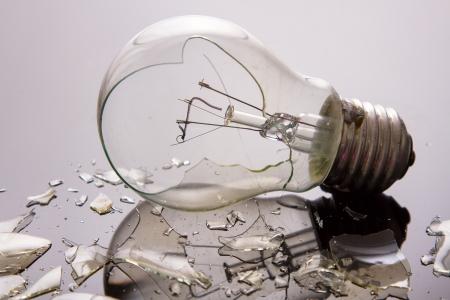 roto: Bombilla quebrada en superficie brillante con piezas retroiluminada