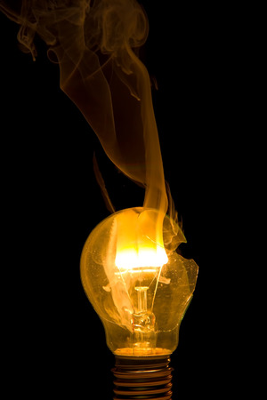 burns: Broken light bulb burn out with flame on filament with smoke Stock Photo