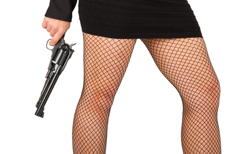 Legs of dangerous woman with handgun and black shoes stockings photo
