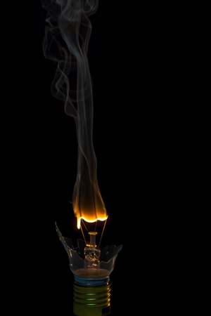 uncontrolled: Broken light bulb burn out with flame on filament with smoke Stock Photo