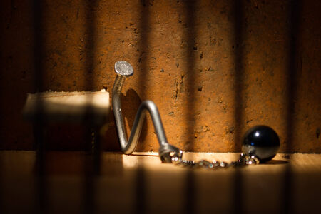 Conceptual jail photo with iron nail ball and chain behind out of focus bars Stock Photo