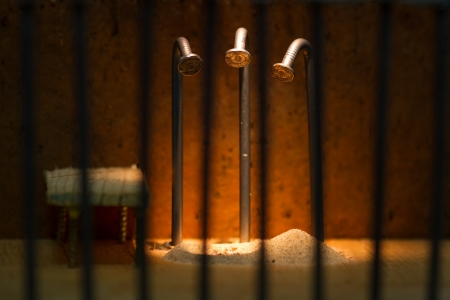 Conceptual jail photo with iron nail escaping behind out of focus bars hole of sand photo