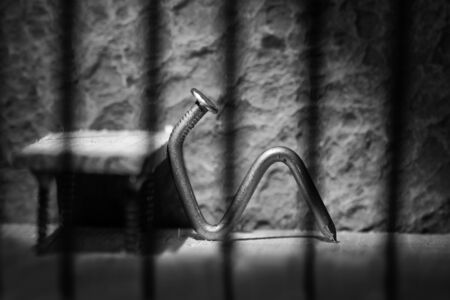 Conceptual jail photo with iron nail sitting behind out of focus bars artistic conversion photo
