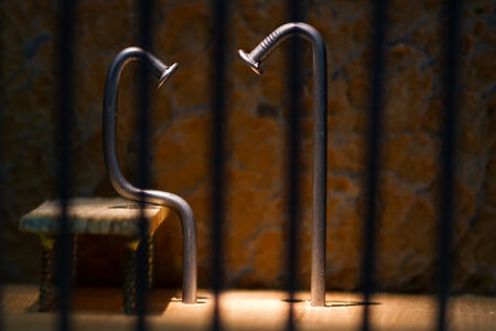 Conceptual jail photo with iron nail sitting behind out of focus bars photo