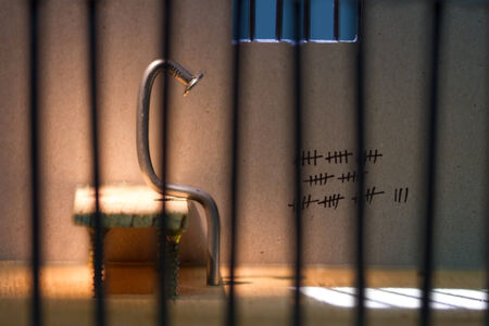 Conceptual jail photo with iron nail sitting behind out of focus bars and window photo