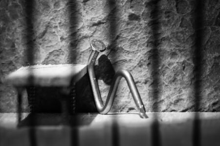 Conceptual jail photo with iron nail sitting behind out of focus bars artistic conversion Stock Photo - 26049248